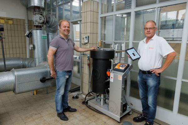"""Eingespieltes Team für die Wärmeversorgung: Tobias Broxtermann (links) und Veolia-Experte Arne Gebken. Im Mittelpunkt: """"BerkeSelect iQ+"""" zur kontinuierlichen Heizwasseraufbereitung im Teilstromverfahren."""
