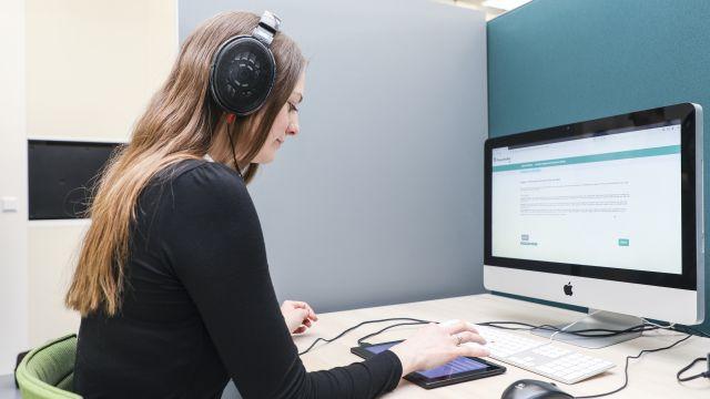 Eine Frau sitzt mit Kopfhörern vor einem Computer an einem Schreibtisch.