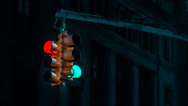 Eine rote und eine grüne Ampel vor einem schwarzen Hintergrund.
