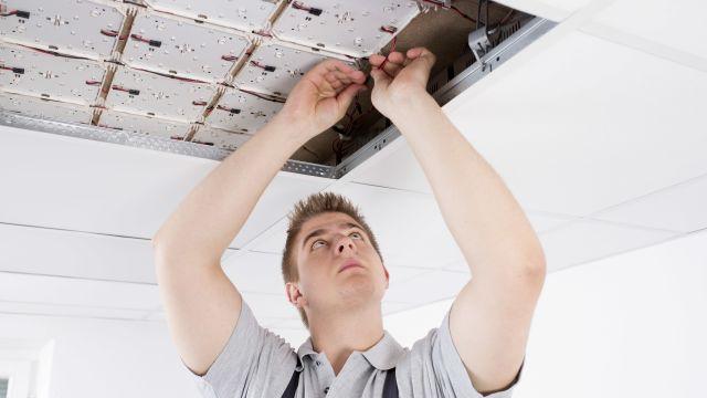 Das Bild zeigt einen Elektroniker, der ein KNX-Kabel an der LED-Beleuchtung an der Decke installiert.