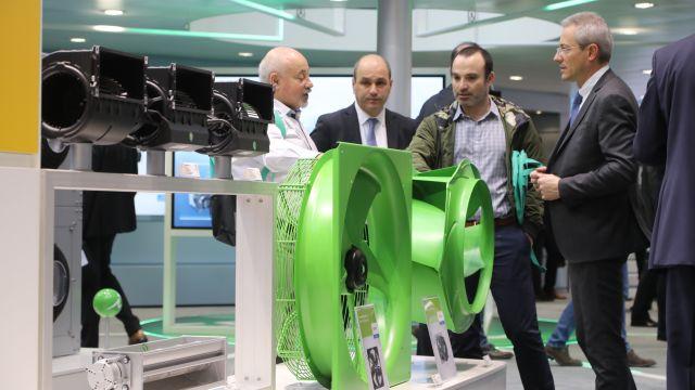 Das Bild zeigt einen Messestand mit raumlufttechnischen Produkten, darunter zwei grüne Ventilatoren, und einige Personen, die diese betrachten.