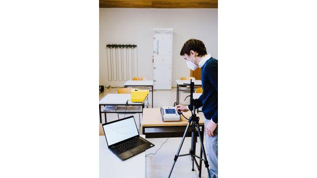 Das Bild zeigt einen Mann mit Atemschutzmaske, der in einem Klassenzimmer mit Hilfe von Messgeräten und einem Laptop eine Messung durchführt. An einer Wand im Hintergrund steht ein Luftreiniger.
