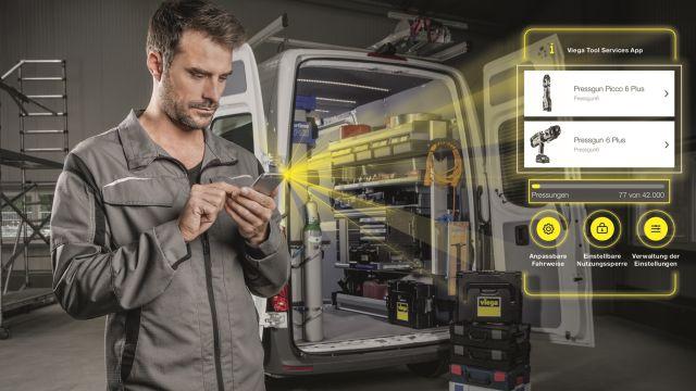 Das Bild zeigt einen Handwerker, der vor einem offenen Transporter mit einem Smartphone in der Hand steht.