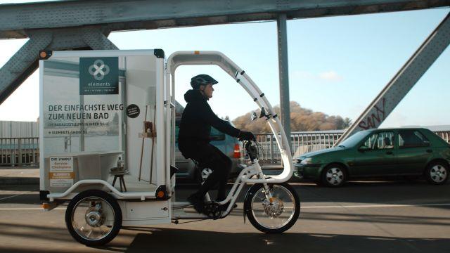 Das Bild zeigt einen Stadtlieferanten auf einem Lastenfahrrad unterwegs auf einer Straße.