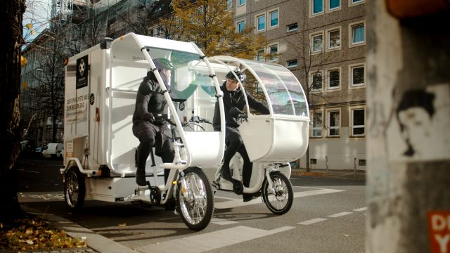 Das Bild zeigt zwei nebeneinander stehende Lastenfahrräder auf einer innerstädtischen Straße. Die Fahrer sitzen auf den Rädern und unterhalten sich miteinander.
