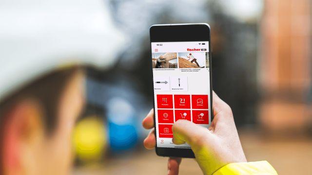 Das Bild zeigt ein Smartphone mit der geöffneten App des Herstellers Fischer auf dem Display, das in der Hand eines Handwerkers mit Helm gehalten wird.