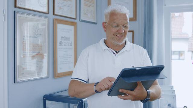 Das Bild zeigt einen Mann, der auf einem großen Tablet, das er in der Hand hält, tippt.
