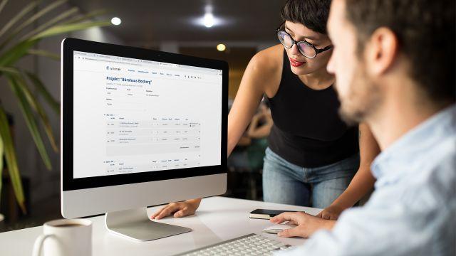 Das Bild zeigt zwei Menschen vor einem Bildschirm.
