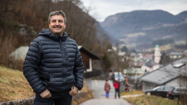 Das Bild zeigt Georg Hackl in Winterjacke gekleidet und auf einem Weg stehend, im Hintergrund das Berchtesgadener Land.