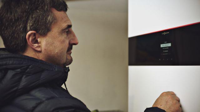 Das Bild zeigt Georg Hackl, der eine Wärmepumpe anschaut.