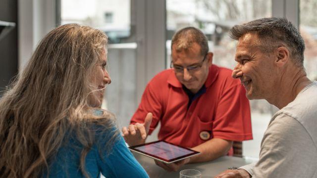 Das Bild zeigt drei Personen in einem Beratungsgespräch