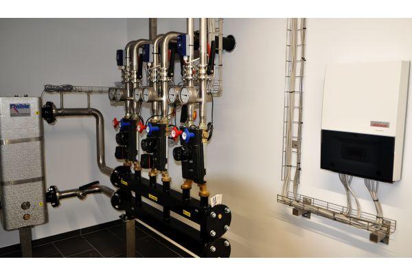 Der Masterregler (re.) kontrolliert und steuert als Energiemanager die Wärmepumpen-Kaskade. Die bedient drei Heizkreise. Links im Bild: die hydraulische Weiche.
