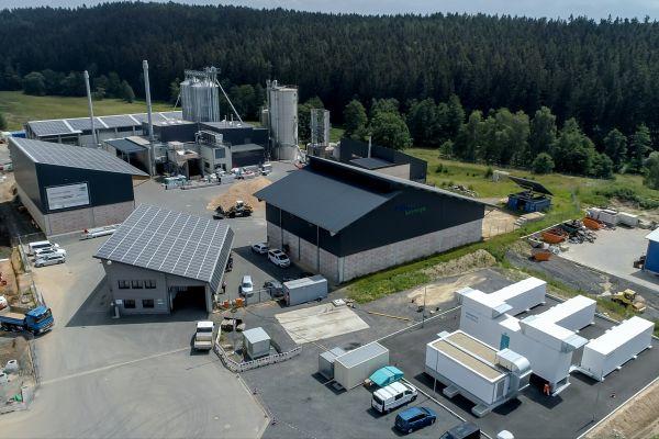 """Der Wasserstoff wird durch die Elektrolyse von Wasser hergestellt. Die für diesen Prozess erforderliche Energie liefert der aus PV- und Windkraftanlagen bereitgestellte Strom. Als sogenannter Elektrolyseur kommt in Wunsiedel ein """"Silyzer 300"""" von Siemens Energy zum Einsatz. Als Besonderheit werden hier auch der bei der Wasserstoff-Erzeugung anfallende Sauerstoff sowie die Niedertemperaturabwärme erstmalig in nahegelegenen Industriebetrieben weiter genutzt."""