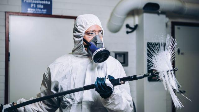 Das Bild zeigt einen Mann in Schutzkleidung mit einer Handbohrerwelle in den Händen.