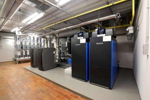 """Die Gas-Brennwertkessel """"Logano plus KB372"""" bilden ein effizientes Duo mit bis zu 600 kW Leistung. Zwei Brennstoffzellen """"BlueGEN BG-15"""", links im Bild, decken die elektrische Grundlast des Gebäudes und sind hydraulisch auch in die Pufferspeicheranlage eingebunden."""