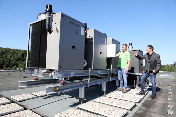 Hoch oben für niedrige Energiekosten: Die Kaskade aus drei Gas-Absorptionswärmepumpen auf dem Flachdach der KGS in Bad Lauterberg. Dass Gas-Wärmepumpen zu den zukunftsfähigen Wärmeerzeugern zählen, darin sind sich Frank Bernkurth, Lodewick GmbH (li.), und Matthias Fiedler, Planungsbüro Breitenstein, einig.