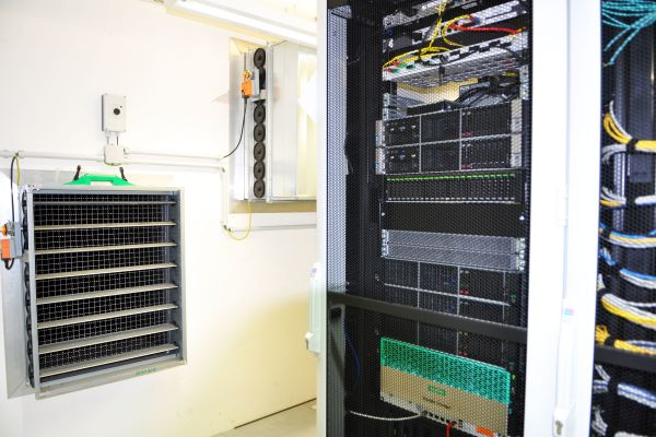 Die Luft/Wasser-Wärmepumpe im Altbau dient auch zur Serverraumkühlung. Aus der Luftkammer hinter der Jalousie strömt Kaltluft.