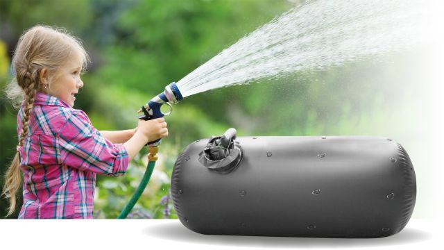 Ein Mädchen spritzt Wasser aus einem Bewässerungsschlauch, daneben ist eine Regenwasser-Innenhülle zu sehen.