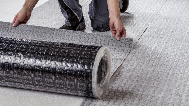 Ein Handwerker verlegt eine Klett-Systemmatte.