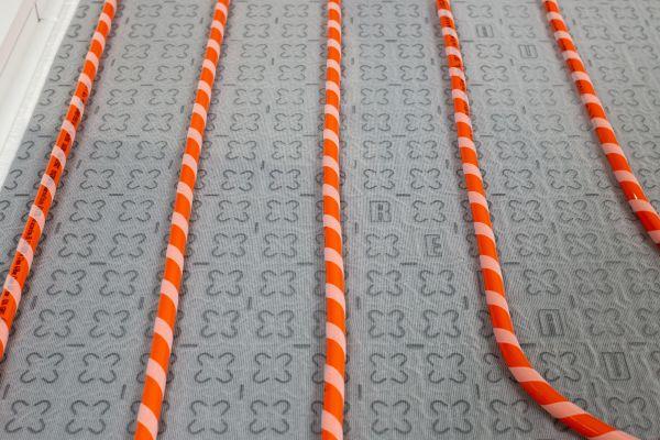 Der Monteur kann das Heizungsrohr im Alleingang von der Abrollvorrichtung abwickeln, mit dem Fuß auf die Matte drücken und so die Bahn sicher verlegen.