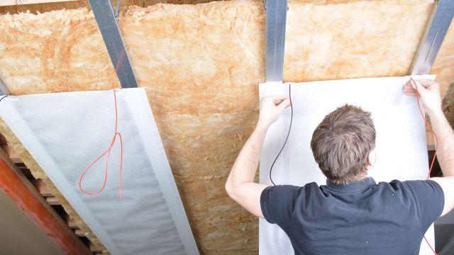 Das Bild zeigt einen Mann beim Befestigen einer Heizfolie an der Decke.