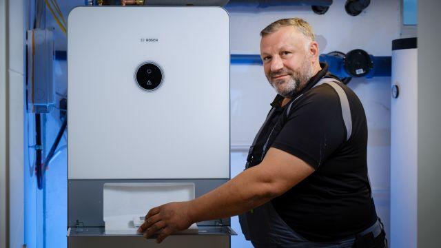Foto: Chef-Installateur der Almo Bauträger GmbH, Hakan Altintas, mit vormontiertem Wärmepumpensystem.