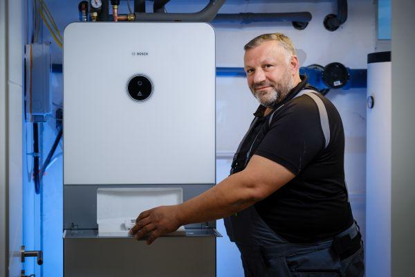 Der Chef-Installateur der Almo Bauträger GmbH, Hakan Altintas, freut sich über die vollständig vormontierte Hydraulik des Wärmepumpensystems.