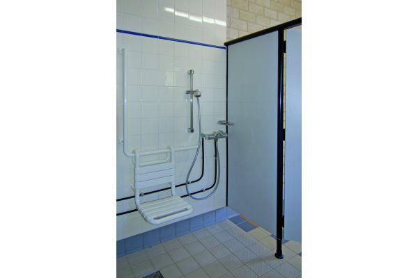 Ein barrierefreier Sanitärraum in einem Schwimmbad inklusive Dusche.