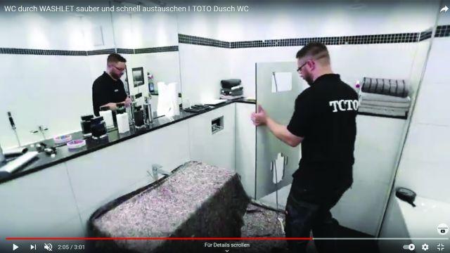 Ein Toto-Experte passt bei der Installation eines Dusch-WC die Verkleidungsplatte an.