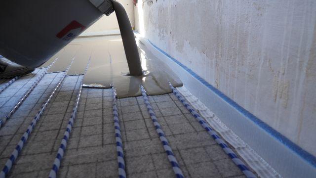 """Foto: Flächenheiz- und -kühlsystem """"Permatop SF"""" bestehend aus der selbstnivellierenden Energieverteilschicht mit integriertem wasserführenden Heiz- und Kühlleiter sowie einem PE-Heizrohr mit Klett-Technologie zur einfachen Verlegung auf der selbstklebenden Fasergewebematte."""
