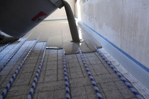 """Das Flächenheiz- und -kühlsystem """"Permatop SF"""" besteht aus der selbstnivellierenden Energieverteilschicht mit integriertem wasserführenden Heiz- und Kühlleiter sowie aus einem PE-Heizrohr mit Klett-Technologie zur einfachen Verlegung auf der selbstklebenden Fasergewebematte."""