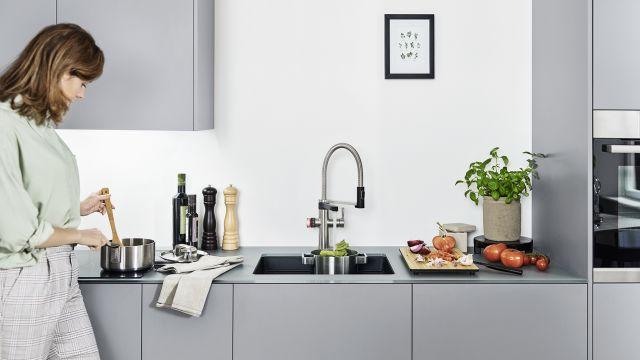 Das Bild zeigt eine Frau an der Küchenspüle.