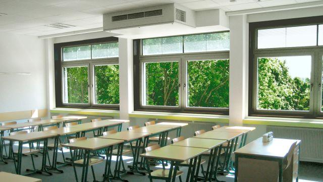 Ein Klassenzimmer mit einem dezentralen Lüftungsgerät an der Decke.