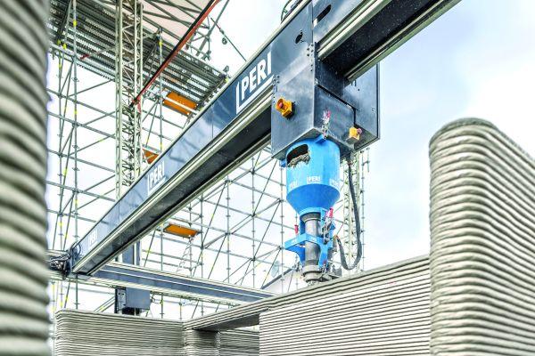 """3D-Druck am Bau in Wallenhausen: Für die Bedienung sind insgesamt zwei Personen notwendig; der Druckkopf und die Druckergebnisse werden per Kamera überwacht. Das eingesetzte Material """"i.tech 3D"""" entwickelte HeidelbergCement speziell für den 3D-Druck."""