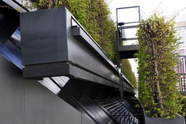 Eine mobile Plattform zwischen den einzelnen Reihen lässt Kontrolle und Wartung zu. Messstationen in der Fassade erfassen das aktuelle Wettergeschehen und steuern danach die Tropfbewässerung.