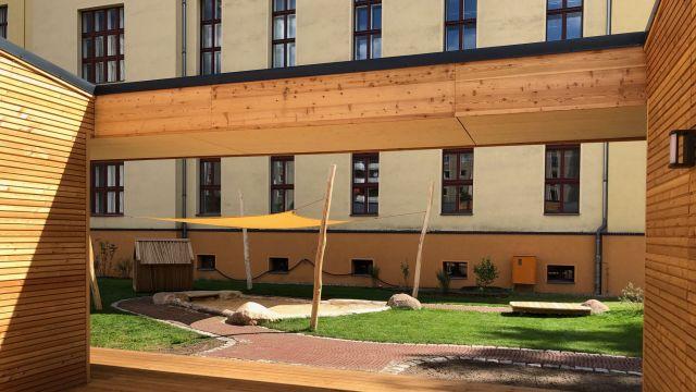 Foto: Der Baukörper wurde so angeordnet, dass im Zusammenspiel mit der umliegenden Bebauung ein Innenhof entsteht. Dieser wird als Außenspielbereich genutzt.