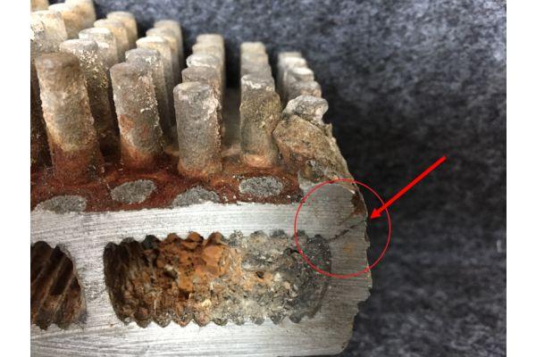 Defekter Wärmeerzeuger aus einer Aluminiumlegierung, der durch eingespülte Korrosionsprodukte und Kalkstein lokal überhitzt hat und gerissen ist.
