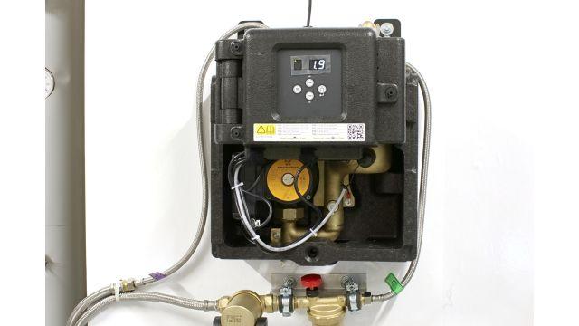 """Foto: Im Zulauf zum """"S250"""" befindet sich ein Schlammabscheider, um den Entgaser vor Verunreinigungen zu schützen. Unter der Dämmschale sitzt das kompakte Gerät: Ein Venturi-Rohr erzeugt in Kombination mit einer drehzahlgesteuerten Kreiselpumpe das Vakuum. An das Venturi-Rohr ist der Entgasungsbehälter aus Messing angeschlossen."""
