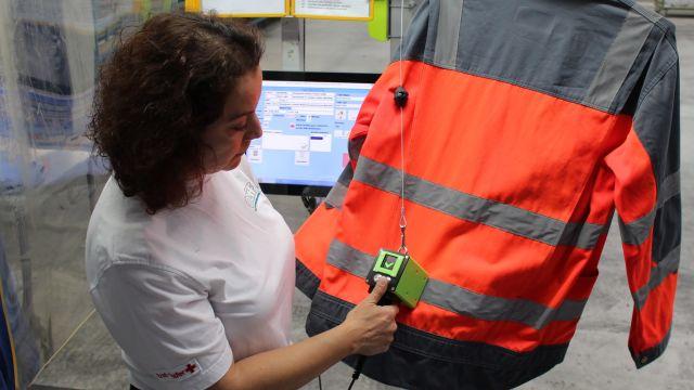 Das Bild zeigt eine Mitarbeiterin, die die Retroreflektion des Reflexstreifens prüft.