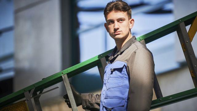Das Bild zeigt einen Mann in Berufskleidung mit einer Leiter.
