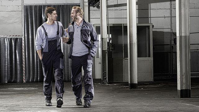 Das Bild zeigt zwei Männer in Arbeitskleidung.