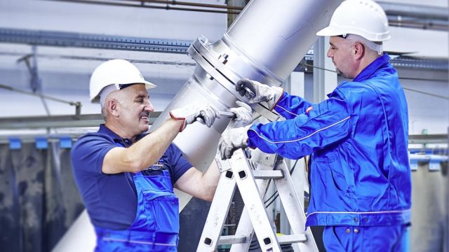 Das Bild zeigt zwei Mitarbeiter mit einem Rohr.