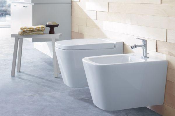 Das Bild zeigt einen Badezimmerausschnitt. Im Vordergrund ist ein wandhängendes Bidet aus weißer Sanitärkeramik von Burgbad zu sehen. Dahinter ist ein wandhängendes WC installiert.