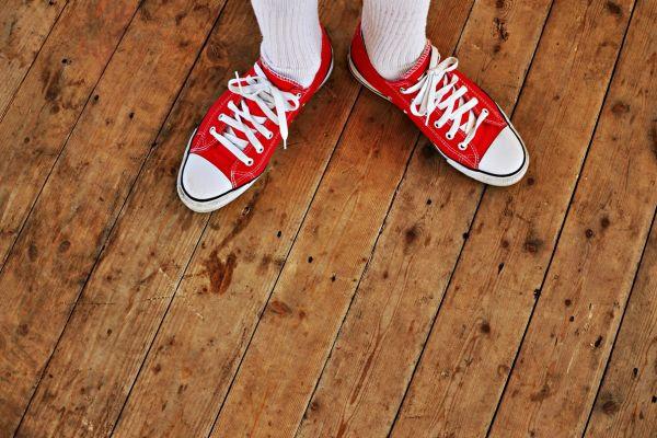 Zwei Füße stehen auf einem Holzboden.