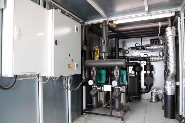 Mobile Kompaktlösung an der Wärmequelle: Am Standort der Biogasanlage baute Yados eine Hydraulikstation mit Wärmeauskopplungsmodul und integrierten Netzpumpen zur Einspeisung in das Wärmenetz in Containerausführung. Das Containersystem ist ortsbeweglich und kann bei Bedarf flexibel umgesetzt werden.