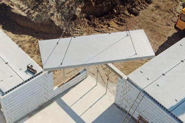 Einbau von Systemfertigdecken mit einem Kran auf einer Baustelle.