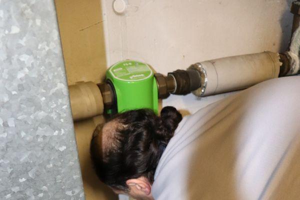 Ein Installateur entfernt eine Filterkerze am Wasserfilter einer Trinkwasser-Anlage.