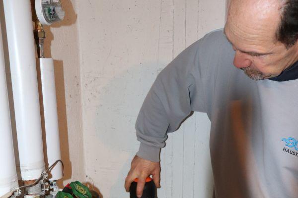 Ein Installateur reinigt einen rückspülbaren Filter an einer Trinkwasser-Anlage.