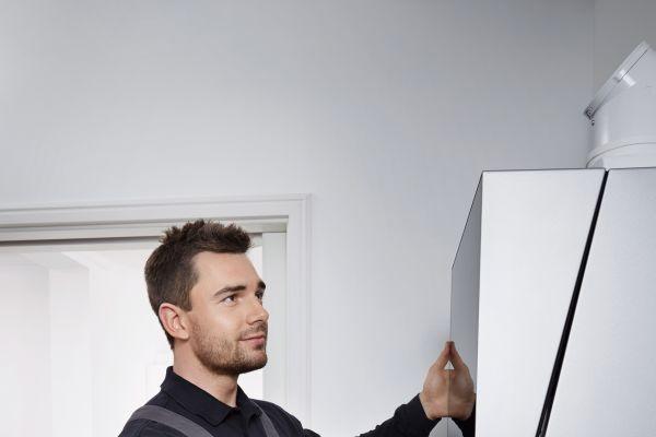 Ein Handwerker befestig die Abdeckung einer Therme.