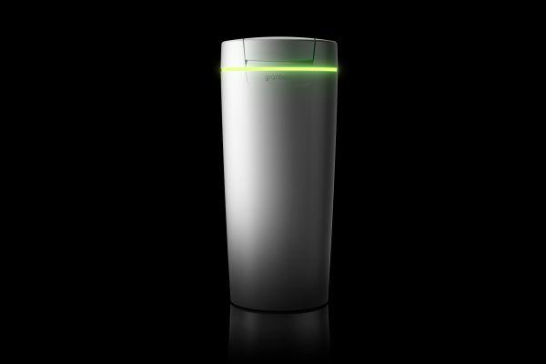 """Das Bild zeigt vor einem schwarzen Hintergrund die weiße Weichwasseranlage """"softliQ:SC23"""" von Grünbeck mit grünem LED-Leuchtring."""